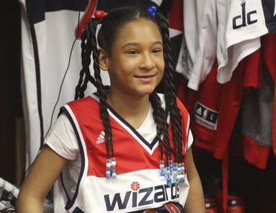 Amaris Jackson poses for pictures in front of John Wall's locker. (Photo courtesy of the Washington Wizards)