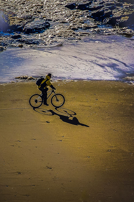 Bicycler on the beach in Lincoln City, Oregon.